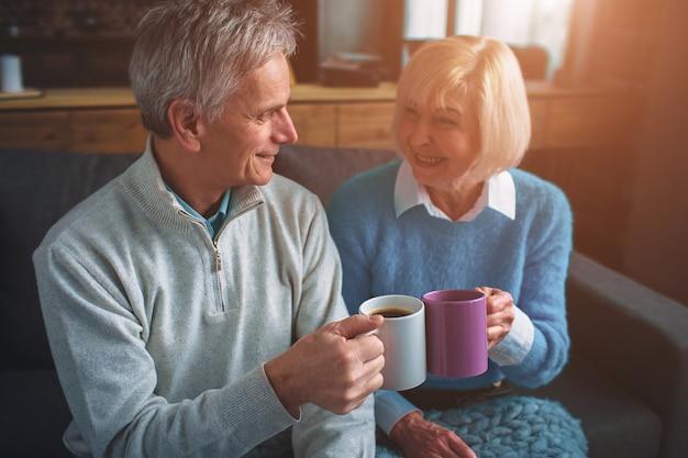 El esposo y la esposa están sentados juntos y beben té de tazas