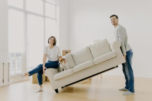 El esposo y la esposa llevan el sofá, amueblan la sala de estar después de la renovación, felices de comprar el apartamento