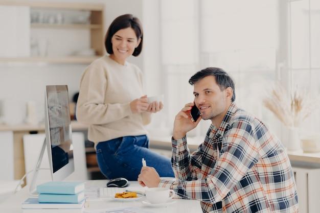 El esposo y la esposa satisfechos administran las finanzas en el hogar, revisan las cuentas bancarias