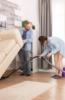 El esposo levanta el sofá para que su esposa limpie el polvo debajo de él con una aspiradora
