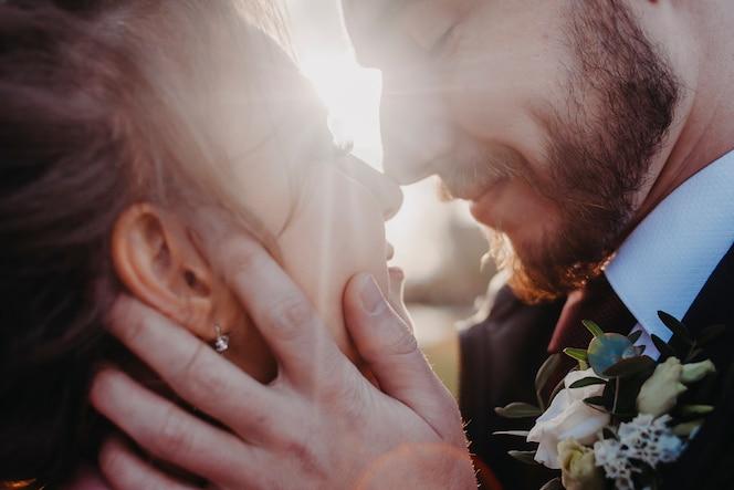 El esposo sostiene a su esposa por la cara contra el telón de fondo de los rayos del sol.