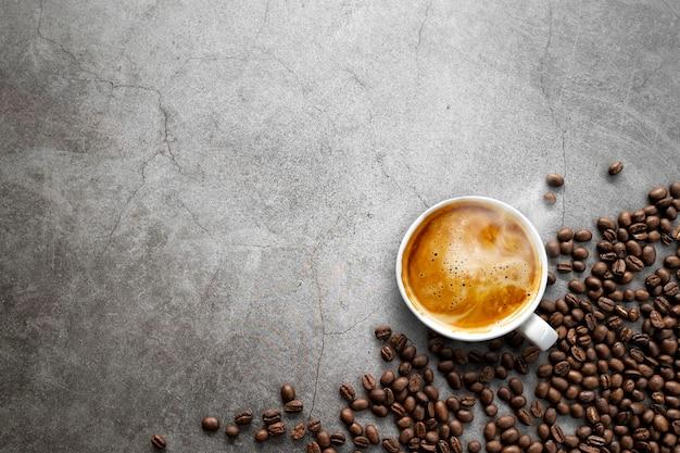 Espresso caliente y granos de café sobre fondo de piso de cemento antiguo