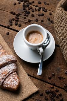Espresso con croissant y semillas de café.