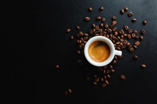 Espresso humeante sabroso en taza con granos de café. vista desde arriba. fondo oscuro.
