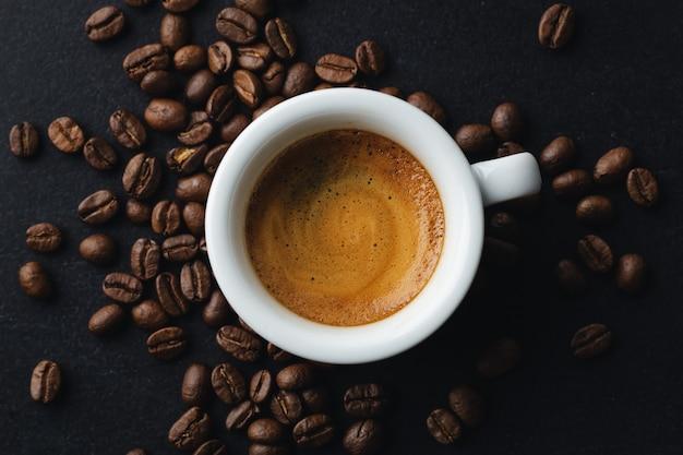 Espresso humeante sabroso en taza con granos de café. vista desde arriba.