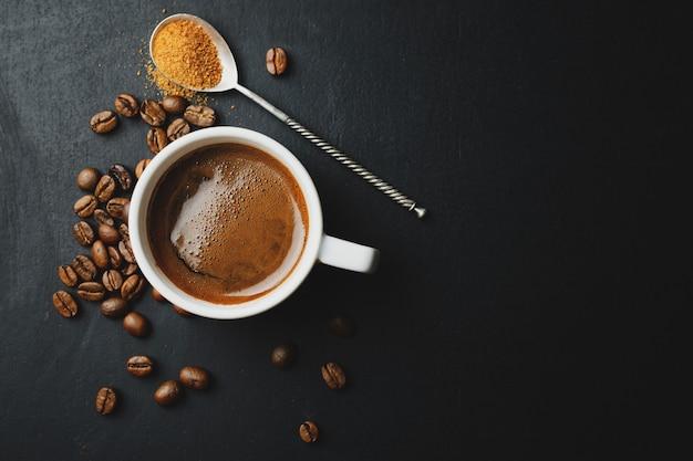 Espresso humeante sabroso en taza con granos de café. vista desde arriba