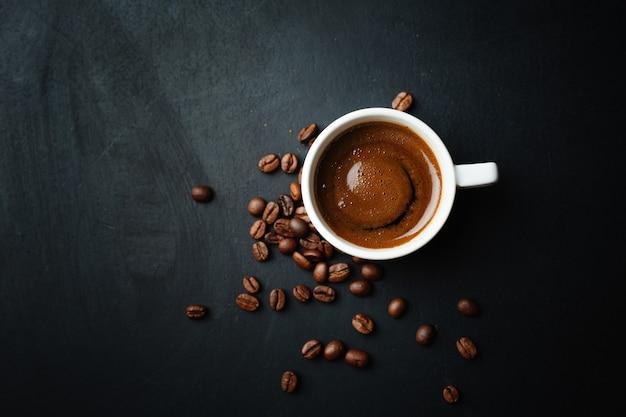 Espresso humeante sabroso en taza con granos de café. vista superior