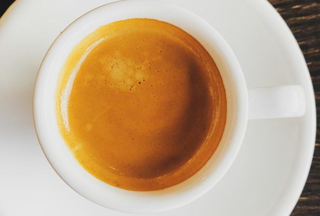 Espresso italiano fresco sabroso en taza de cerámica blanca en la mesa de café