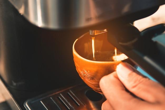 Espresso que vierte de la máquina de café