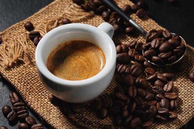 Espresso sabroso servido en taza con granos de café alrededor y cuchara. de cerca. fondo oscuro.