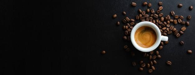 Espresso sabroso servido en taza con granos de café alrededor y cuchara. vista desde arriba. fondo oscuro. bandera.