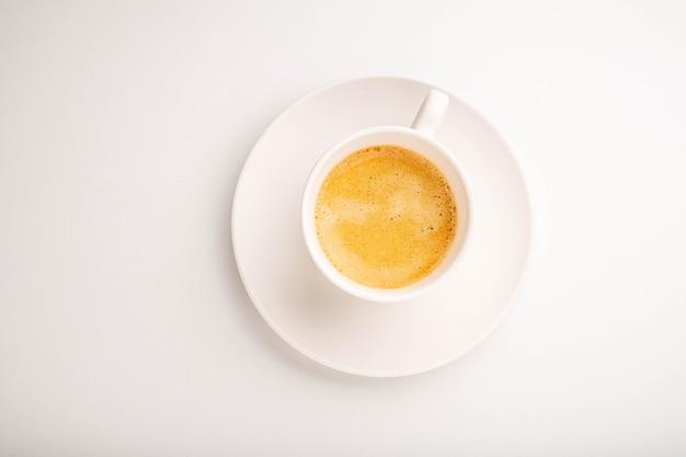Espresso en una taza blanca sobre un fondo blanco. vista desde arriba