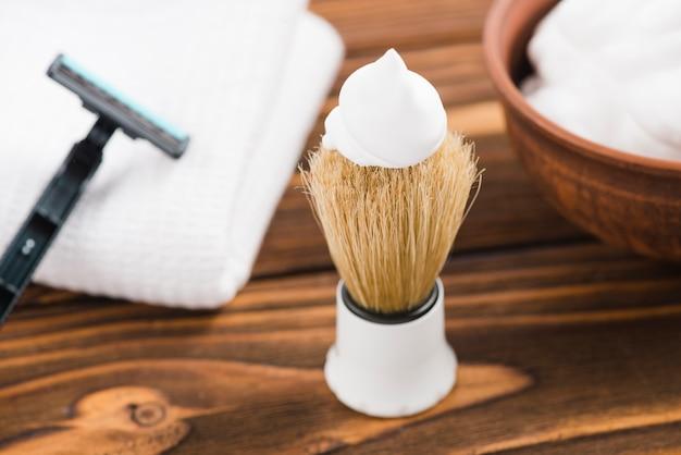 Espuma blanca sobre la brocha de afeitar con maquinilla de afeitar; servilleta y espuma sobre el escritorio.