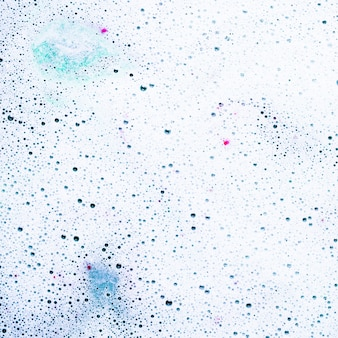 Espuma y burbujas en la superficie de la bomba de baño en agua.