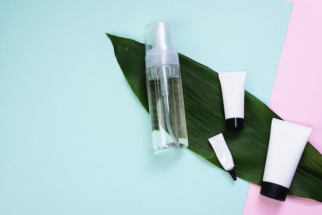 Espuma limpiadora o agua micelar y una variedad de cremas en una hoja de palma sobre un fondo rosa pastel y azul. crema para cara, ojos y manos sobre un fondo moderno.