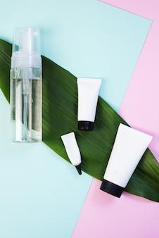 Espuma limpiadora o agua micelar y una variedad de patrones para cremas en una hoja de palma sobre una superficie de color rosa pastel y azul. crema para rostro, ojos y manos sobre una superficie moderna.