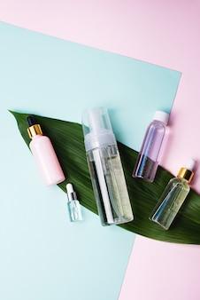 Espuma limpiadora o agua micelar y una variedad de sueros hidratantes sobre una superficie en colores pastel y hojas de palma.