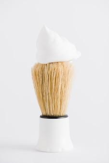 Espuma sobre la brocha de afeitar sintética sobre fondo blanco.