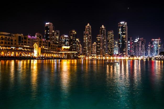 Espumosos dubai rascacielos reflejan en el agua por la noche