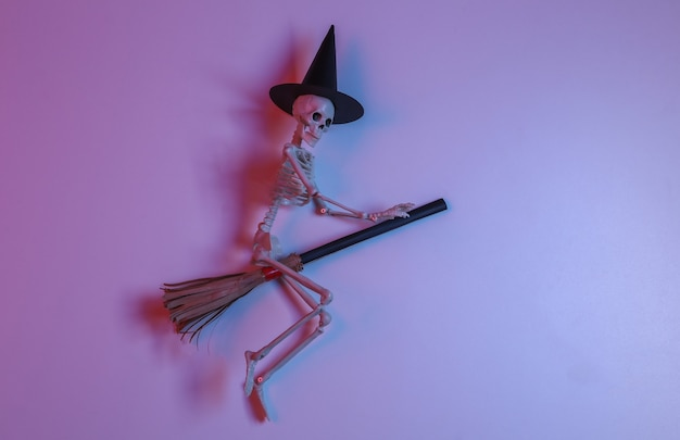 Esqueleto de bruja en una escoba en luz roja-azul neón degradada. tema de halloween
