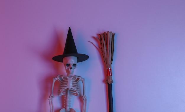 Esqueleto de bruja con palo de escoba en luz roja-azul neón degradada. tema de halloween