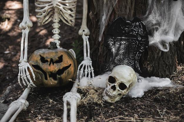 Esqueleto con calabaza sentada cerca de cráneo y lápida apoyándose en el árbol