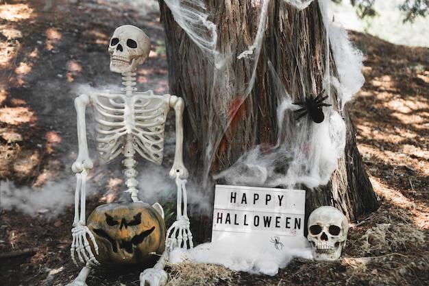 Esqueleto con calabaza sentado en la niebla cerca de la tableta apoyándose en el árbol