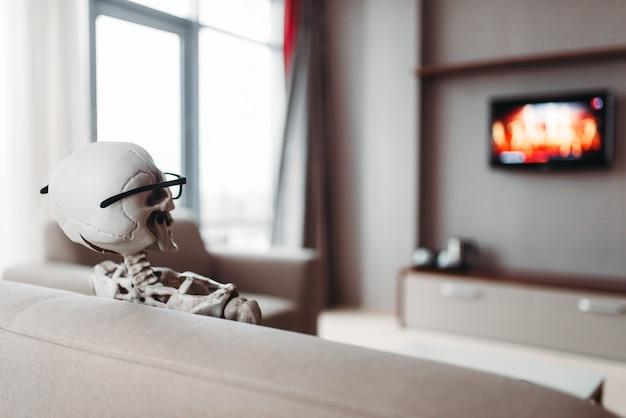 Esqueleto con gafas está sentado en el sofá y ve la televisión, vista posterior