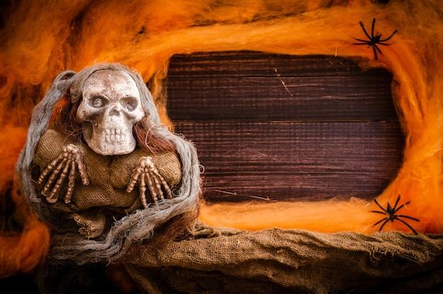 Esqueleto de hueso con tela de araña en el tablero de madera. feliz concepto de halloween