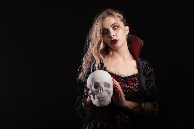 Esqueleto humano sostenido por una hermosa mujer vestida como un vampiro sexy para halloween. maquillaje de halloween.
