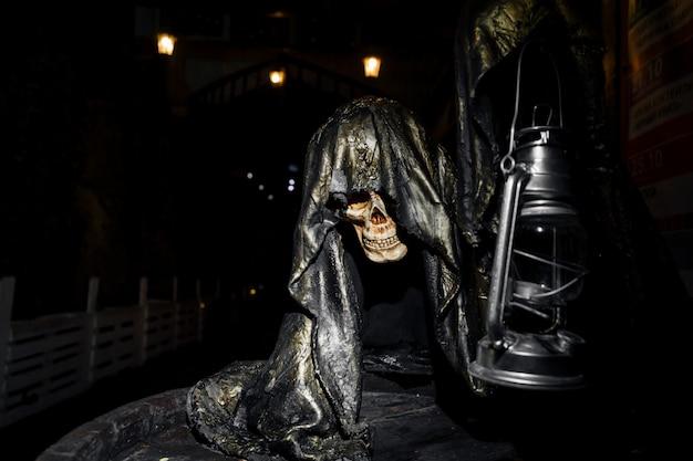 Un esqueleto muy espeluznante que sostiene una lámpara en la mano.