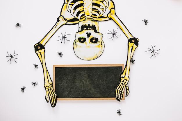Esqueleto rodeado de arañas con tablero