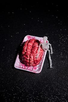 Esqueleto sentado al lado de una composición cerebral