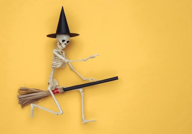 Esqueleto con sombrero de bruja y palo de escoba. fondo amarillo. concepto minimalista de halloween. vista superior. endecha plana