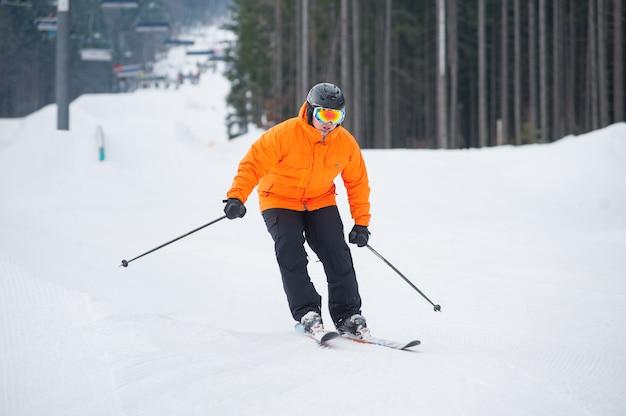 Esquí esquiador cuesta abajo en la estación de esquí contra el remonte