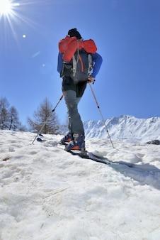 Esquí de turismo bajo el cielo soleado