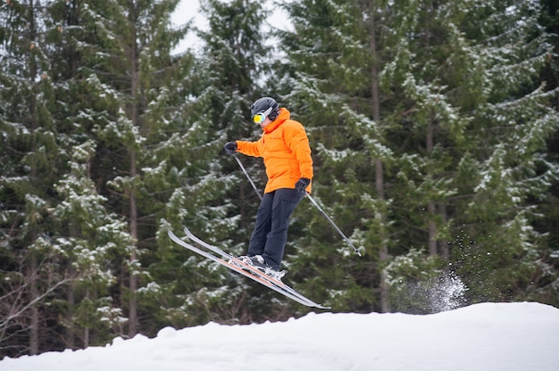 Esquiador al salto desde la ladera de las montañas.
