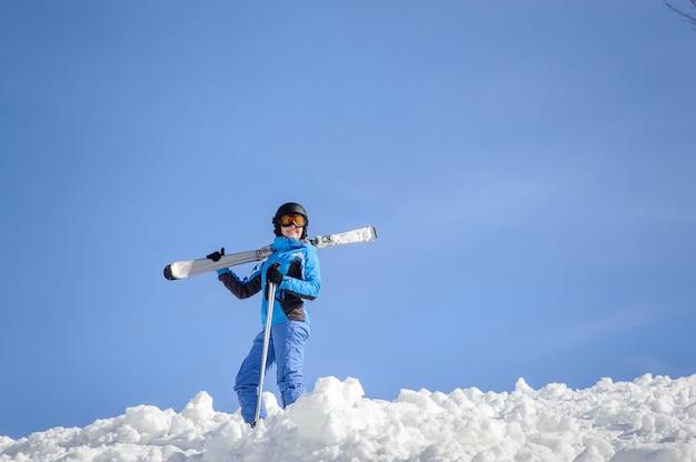 Esquiador femenina de pie en la cima de la montaña
