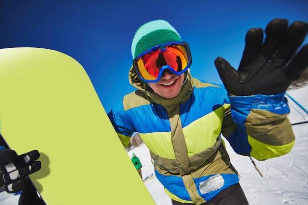 Esquiador joven de snowboard sosteniendo su tabla