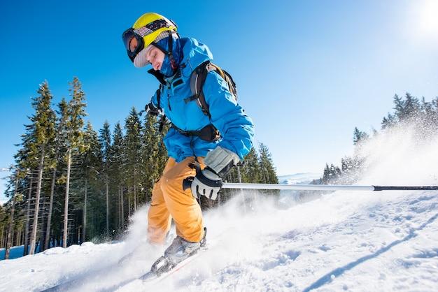 Esquiador masculino esquiando sobre nieve fresca en las montañas en un hermoso día soleado