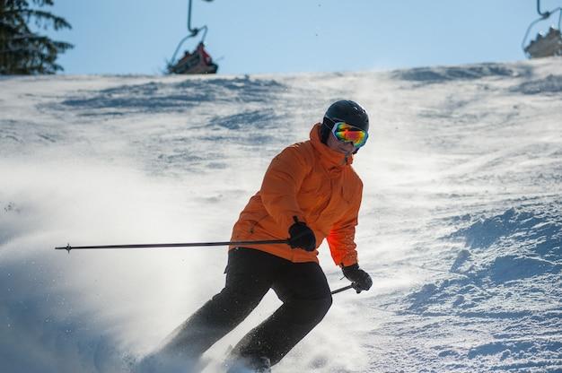 Esquiador masculino esquiar cuesta abajo en la estación de esquí contra el remonte
