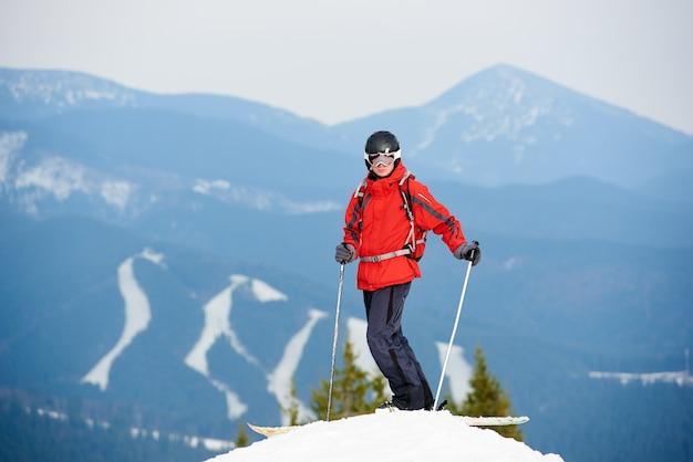 Esquiador masculino de pie en la cima de la pendiente en la estación de esquí de invierno