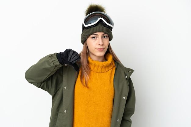 Esquiador mujer caucásica con gafas de snowboard aislado sobre fondo blanco mostrando el pulgar hacia abajo con expresión negativa