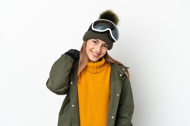 Esquiador mujer caucásica con gafas de snowboard aislado sobre fondo blanco riendo