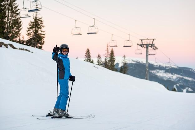 Esquiador de mujer de pie en la montaña de nieve y mostrando los pulgares para arriba