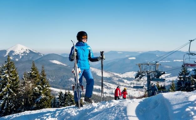 Esquiador de mujer en ropa deportiva de invierno de pie en la cima de una montaña con sus esquís en la estación de esquí de invierno