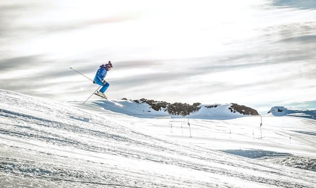 Esquiador profesional realizando salto acrobático en exhibición cuesta abajo