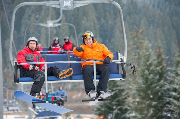 Esquiador y snowboarder montando en remonte