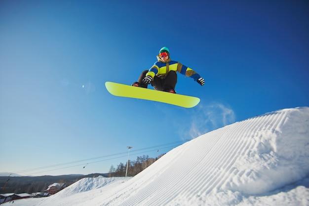 El esquiador de snowboarder saltando a través del cielo azul