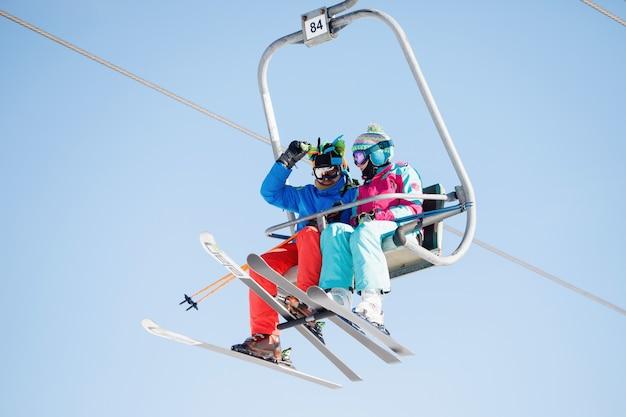 Esquiadores brillantes viajan en las cabinas del teleférico de la estación de esquí